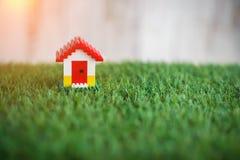 Modello della costruzione di casa di plastica sull'erba jpg Fotografie Stock