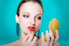 Modello della donna che applica rossetto rosso Fotografia Stock