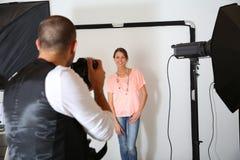 Modello della donna della fucilazione del fotografo in studio Immagine Stock
