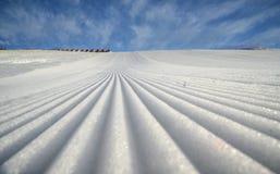 Modello della neve sul pendio dello sci con il fondo del cielo fotografia stock libera da diritti