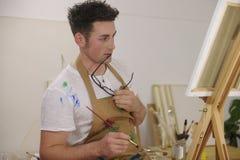 Modello della pittura dell'artista allo studio di arte Immagini Stock