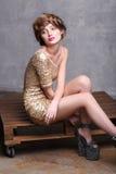 Modello della ragazza che indossa i sandali lussuosi del vestito e della piattaforma dall'oro fotografia stock libera da diritti