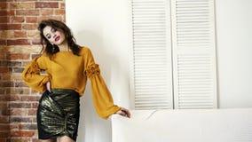 Modello della ragazza in vestiti alla moda e scarpe a tacco alto in studio che posa sulla macchina fotografica con trucco espress