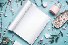 Modello della rivista o del catalogo aperta per bellezza e prodotti del cosmetico sul desktop blu pastello immagini stock libere da diritti