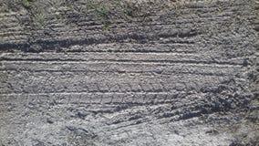 Modello della stampa del pneumatico del camion dell'automobile sulla sabbia nera sporca Fotografie Stock Libere da Diritti