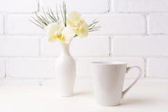 Modello della tazza del latte del caffè macchiato con l'orchidea gialla molle in vaso fotografie stock