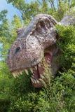Modello della testa del dinosauro di T-Rex fra vegetazione dentro un parco in Ital immagine stock