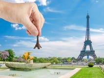 Modello della torre Eiffel in mano del ` s dell'uomo contro la torre Eiffel Fotografie Stock