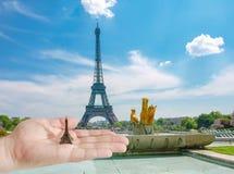 Modello della torre Eiffel sulla palma del ` s dell'uomo contro la torre Eiffel Fotografia Stock Libera da Diritti