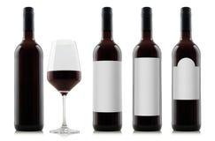 Modello delle bottiglie del vino rosso con le etichette in bianco di bianco e un bicchiere di vino fotografie stock libere da diritti