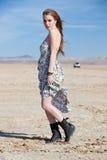 Modello in deserto con l'automobile nella distanza Fotografia Stock
