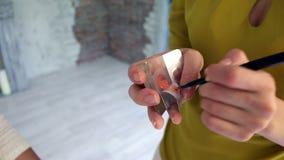 Modello di bellezza che applica rossetto rosso con la spazzola su bianco archivi video
