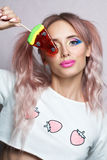 Modello di bellezza con l'acconciatura rosa della coda di cavallo due che mangia lecca-lecca colourful Fotografia Stock Libera da Diritti