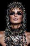 Modello di bellezza di alta moda con la cappelleria metallica ed il trucco scuro e occhi azzurri su fondo nero Fotografia Stock