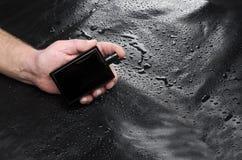 Modello di bootle completamente nero con profumo contro fondo di cuoio Uomo che tiene fragranza immagine stock