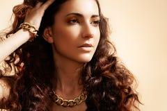 Modello di fascino con i monili lucidi dell'oro, capelli del volume Immagine Stock