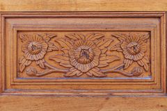 Modello di fiore che scolpisce con lo stile tailandese sulla parete di legno nel tem Fotografia Stock