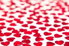 Modello di giorno di biglietti di S. Valentino dei coriandoli rossi dei cuori con sfuocatura su fondo bianco Fotografia Stock