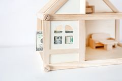 Modello di legno della casa con la banconota in dollari 100 Affitto e vendita della Camera Spese e costi per il trattamento della Immagini Stock