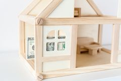 Modello di legno della casa con la banconota in dollari 100 Affitto e vendita della Camera Spese e costi per il trattamento della Fotografia Stock