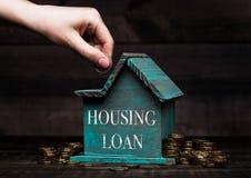 Modello di legno della casa con le monete accanto ed alla mano Immagini Stock Libere da Diritti