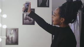 Modello di moda che fa lo specchio della parte anteriore del fronte di trucco della foto del selfie nello spogliatoio archivi video