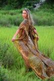 Modello di moda che posa al vestito animale d'uso dalla località di soggiorno della stampa del campo di erba Fotografie Stock Libere da Diritti