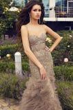 Modello di moda con capelli scuri in vestito lussuoso che posa al giardino Immagini Stock