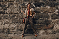Modello di moda In Fashionable Clothes bella donna vicina della parete Fotografia Stock Libera da Diritti