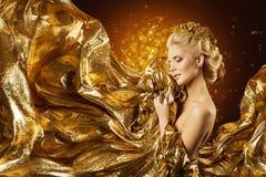 Modello di moda Gold Fabric, fronte della donna e panno dorato volante Fotografie Stock