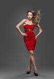 Modello di moda Hair Waving Wind, giovane donna che posa vestito rosso fotografie stock