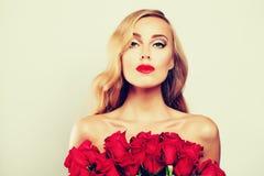 Modello di moda Holding Roses Flowers della donna fotografia stock libera da diritti