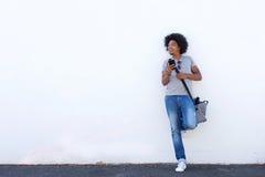 Modello di moda maschio con l'afro che sta con il telefono cellulare Fotografia Stock Libera da Diritti