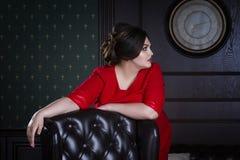 Modello di moda più di dimensione in vestito da sera rosso, donna grassa sull'interno di lusso, ente femminile di peso eccessivo Fotografie Stock Libere da Diritti