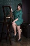 Modello di moda più di dimensione in vestito da sera verde, donna grassa sull'interno di lusso, ente femminile di peso eccessivo Immagine Stock