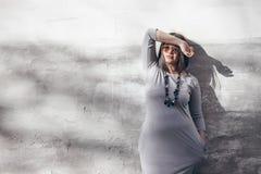 Modello di moda più di dimensione sopra la parete grigia della via fotografia stock