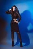 Modello di moda snello in vestiti neri su un fondo blu Fotografia Stock Libera da Diritti