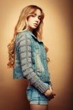 Modello di moda in vestiti piacevoli che posano nello studio su fondo giallo Fotografie Stock Libere da Diritti