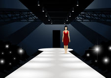 Modello di moda in vestito rosso che cammina giù una passerella Immagini Stock