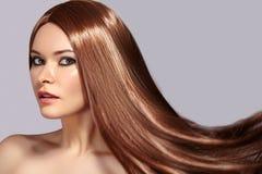 Modello di moda Woman con bei capelli di salto lunghi Donna sexy di fascino con sano e bellezza che pilota i capelli di Brown fotografia stock