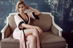 Modello di modo con capelli biondi Giovane donna attraente, collocante sul sofà, stile d'annata Immagine Stock
