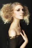 Modello di modo con capelli ricci in tunica nera Fotografie Stock