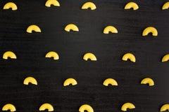 Modello di un mucchio dei corni della pasta su fondo nero fotografie stock libere da diritti