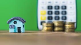 Modello di una casa blu con le monete sui precedenti del calcolatore Fotografie Stock Libere da Diritti
