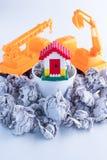 Modello domestico nel concetto di rischio di investimento immobiliare del canestro dei rifiuti Fotografia Stock