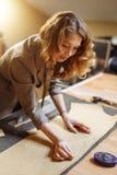 Modello femminile adulto professionale del panno della marcatura del sarto con gesso all'officina di cucito e l'esame della macch fotografie stock