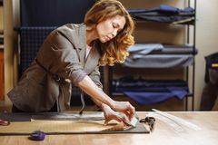 Modello femminile adulto professionale del panno della marcatura del sarto con gesso all'officina di cucito e l'esame della macch fotografia stock
