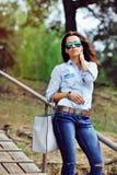 Modello femminile attraente con il ritratto all'aperto di modo della borsa immagine stock