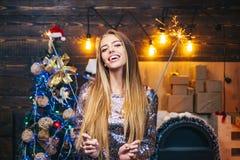 Modello femminile biondo vestito in un cappello di Santa Claus euphoria Giovane donna sveglia con il cappello di Santa Modello Gi immagini stock