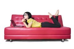 Modello femminile con il computer portatile che fantastica sul sofà Immagine Stock